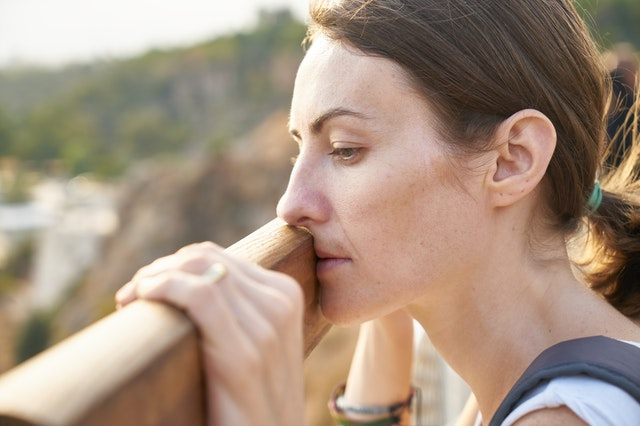 Woman peering over a balcony, looking sad and wistful.